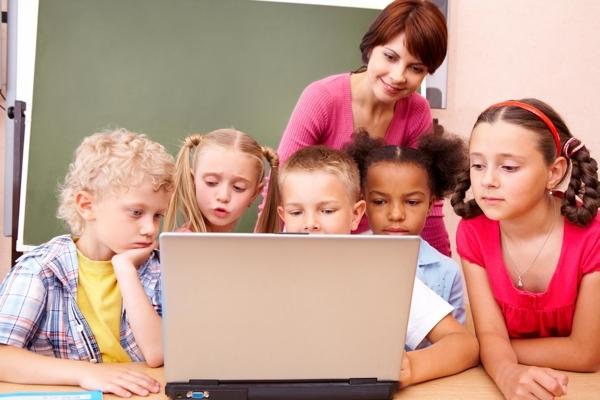 niños y profesora en clase usando un ordendor