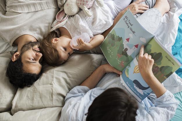 padres leyendo libro a su hija