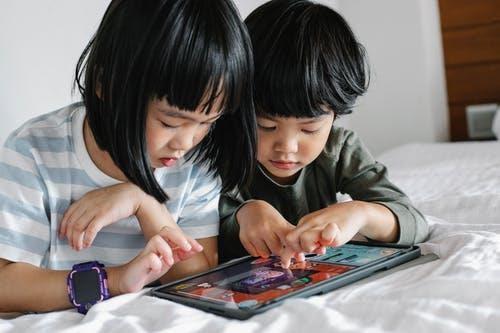 niña y niño jugando a juegos educativos online